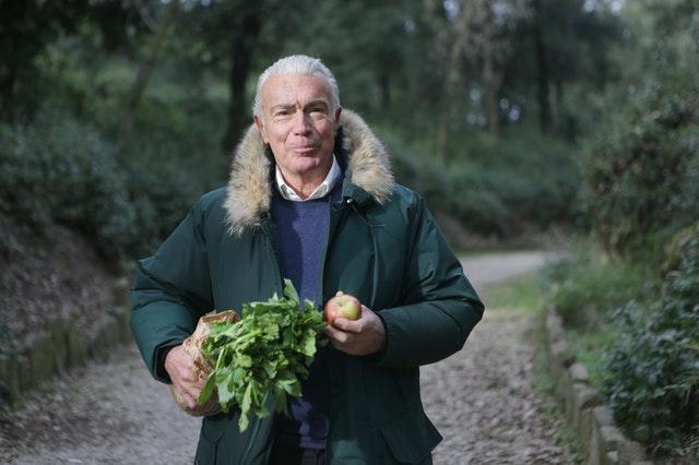 old man holding vegetables